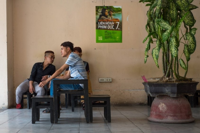 Three young men enjoying Vietnamese coffee and cigarettes on a hot Hue afternoon.