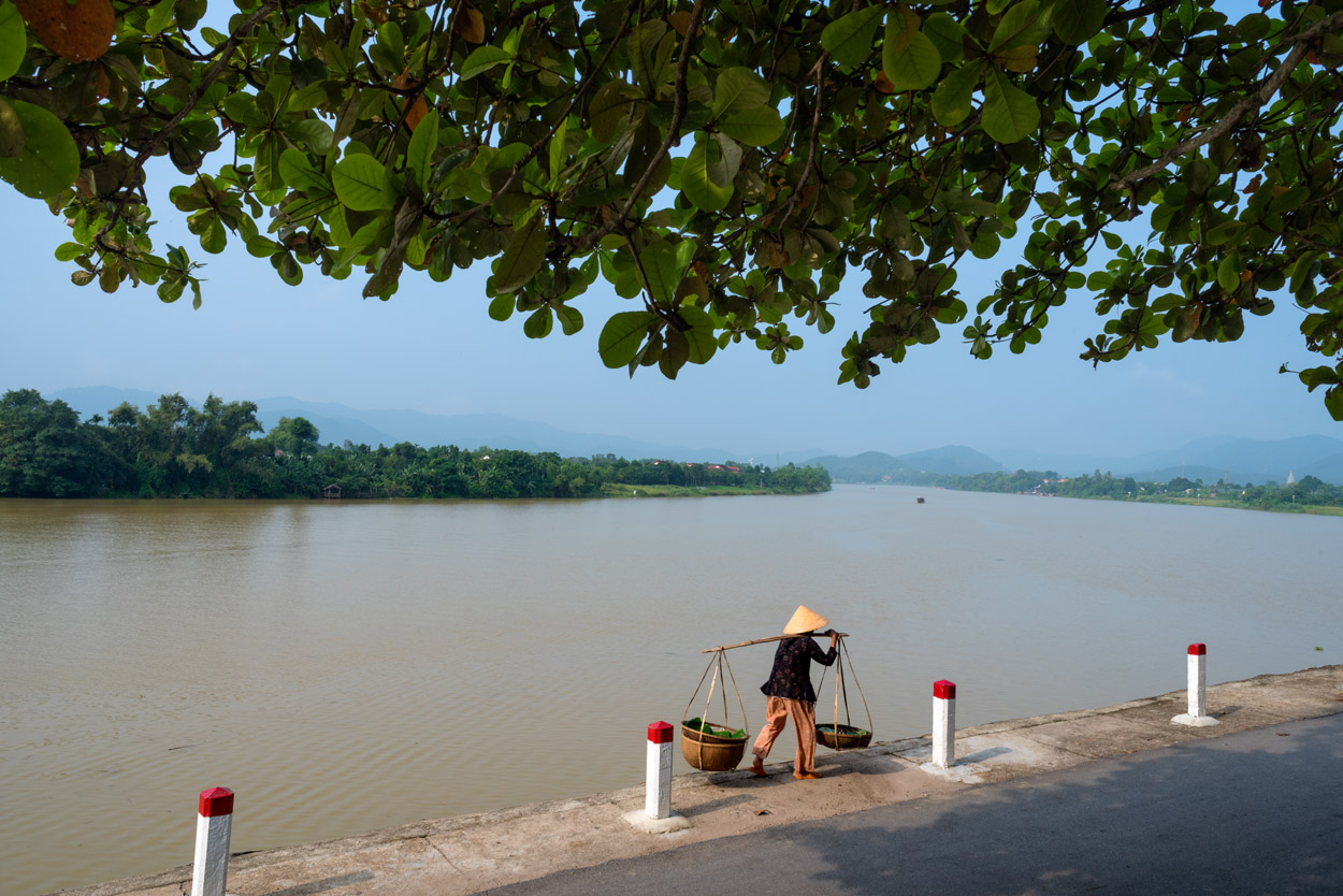 This Vietnamese women is carrying her baskets by the banks of the Perfume River in Hue.